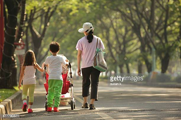 Mom taking young children on morning walk