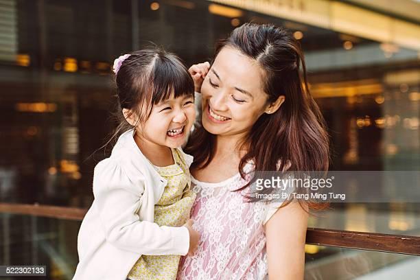 Mom talking joyfully to toddler girl in mall