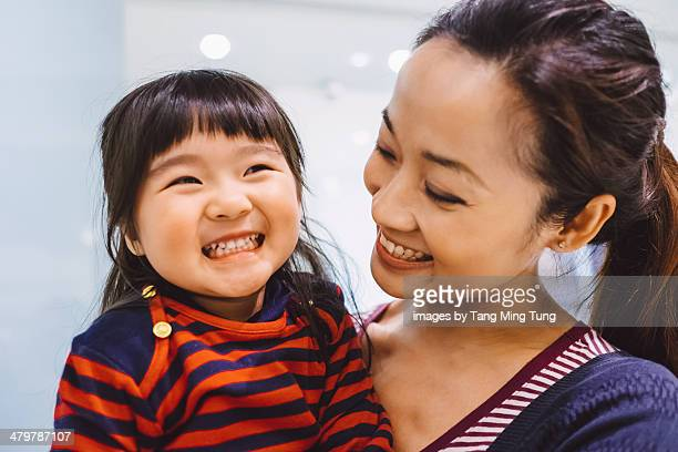 Mom talking joyfully with toddler girl in mall