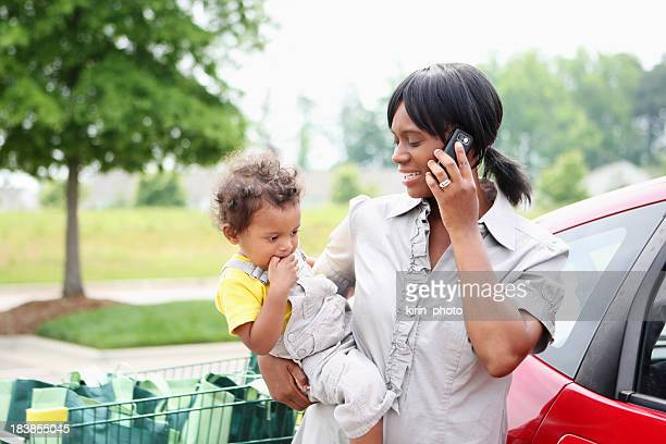 Mom talking on phone next to her car while holding toddler