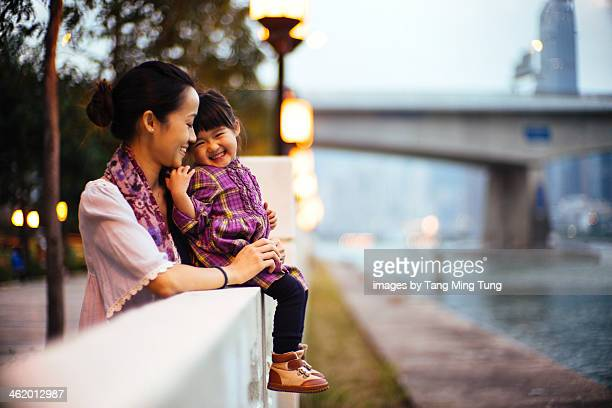 Mom talking to toddler joyfully on promenade
