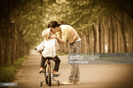 Mom taught his son in the park riding a bike : Stock Photo