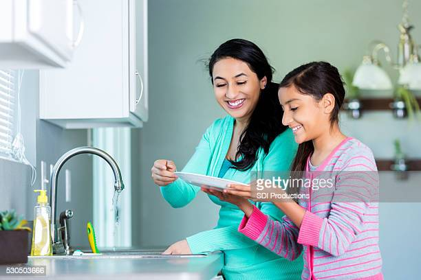 Mom teaches daughter to wash dishes
