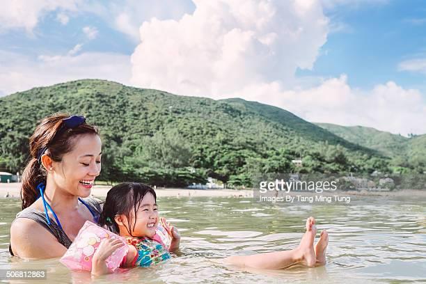 Mom teaching child to swim in sea