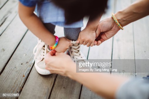 Mom teaching little girl to tide her shoelace
