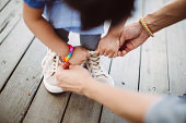 Mom teaching little girl to tide her shoelace