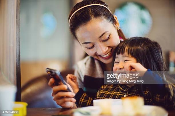 Mom & toddler girl looking at smartphone joyfully