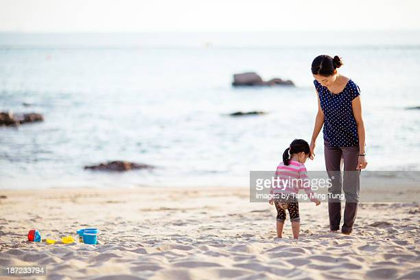Mom & toddler girl looking for sea shells on beach