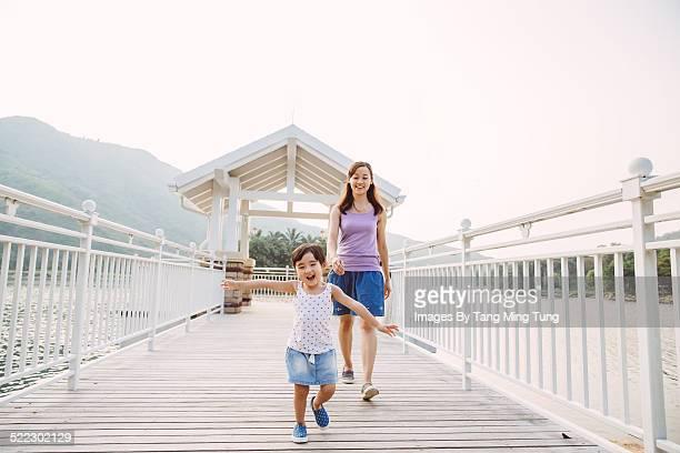 Mom & toddler girl playing joyfully in park