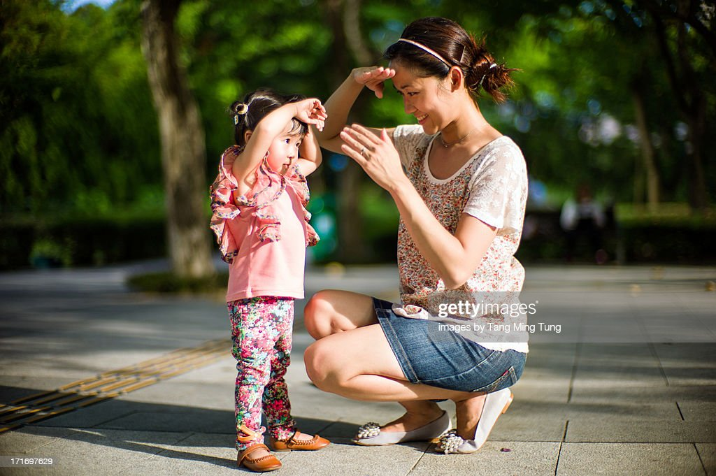 Mom & toddler girl putting their hands over eyes : Stock Photo