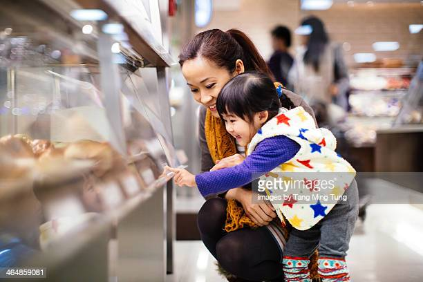 Mom & toddler girl shopping bread in the bakery