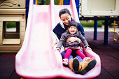 Mom & toddler girl sliding joyfully in playground