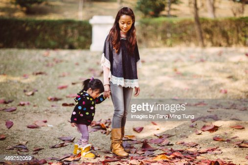 Mom & toddler girl strolling on lawn in park : Stock Photo