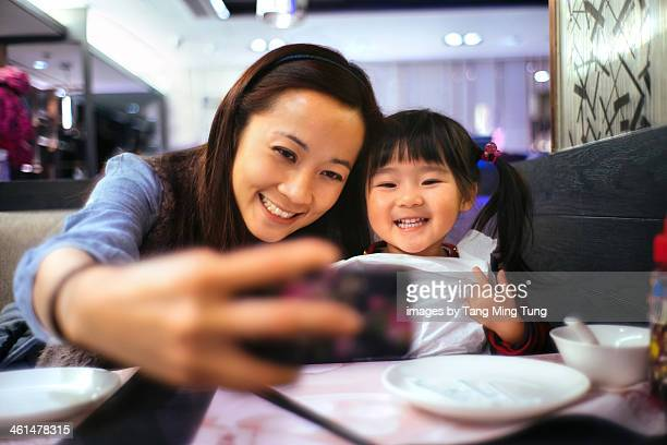 Mom & toddler girl taking selfie in the restaurant