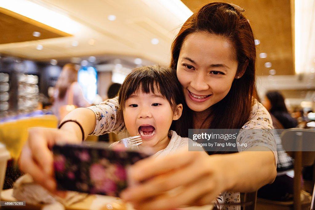 Mom & toddler girl taking selfie joyfully in cafe : Stock Photo