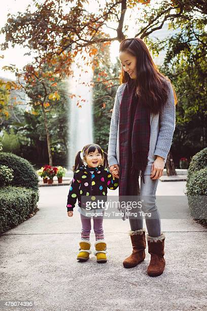 Mom & toddler girl talking joyfully in park
