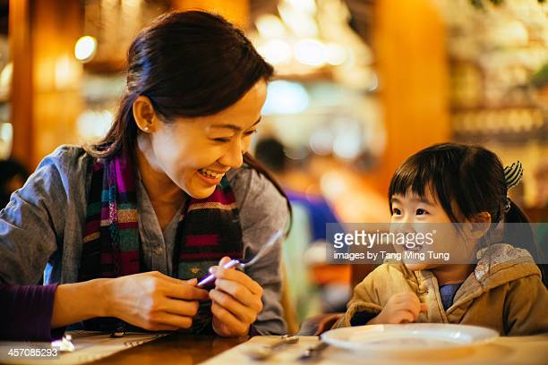 Mom & toddler girl talking joyfully in restaurant
