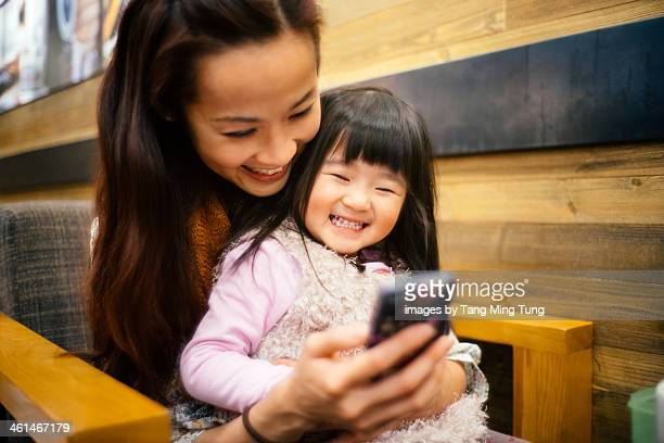 Mom & toddler girl using smartphone joyfully