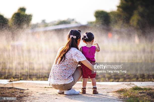 Mom & toddler girl watching the crop irrigation