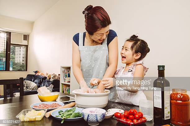 Mom & toddler mixing dough joyfully at home