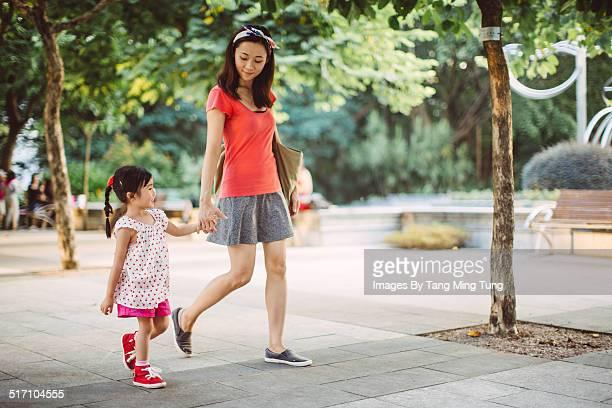 Mom & toddler strolling joyfully in park