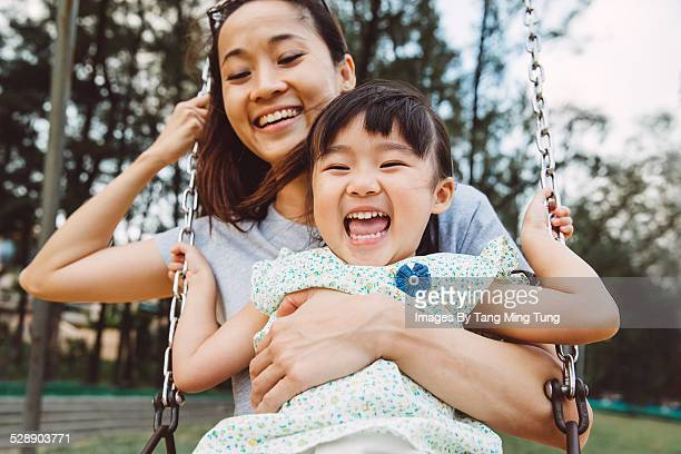 Mom & toddler swinging on swing joyfully in park