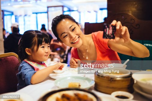 Mom & toddler taking selfie in Chinese restaurant