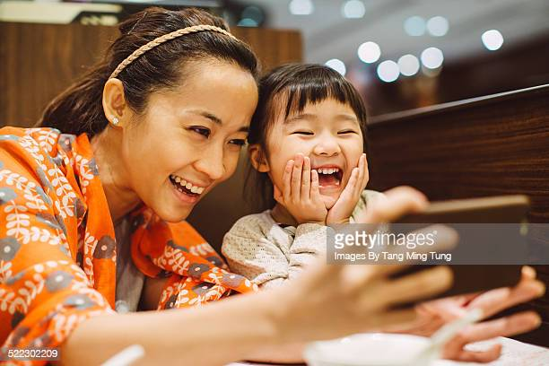 Mom & toddler taking selfies in restaurant