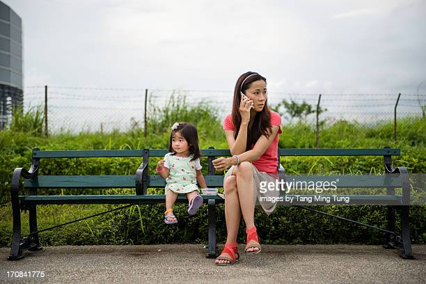 Mom & toddler talking a rest sitting on bench
