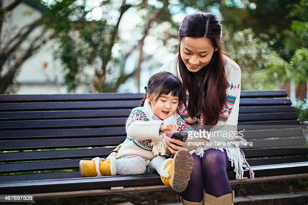 Mom & toddler using smartphone in park