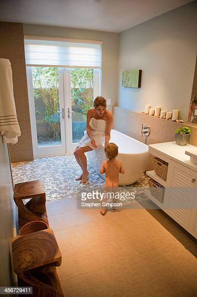 mom trying to coax her small son into the bath tub