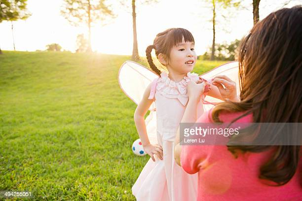 Mom tying wings on kid's dress at park