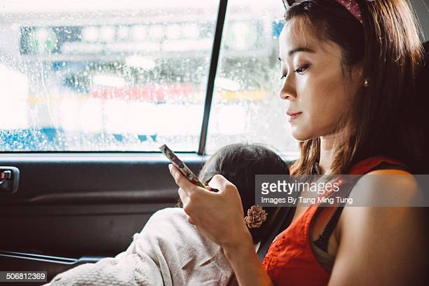 Mom using smartphone with sleeping child in a cab