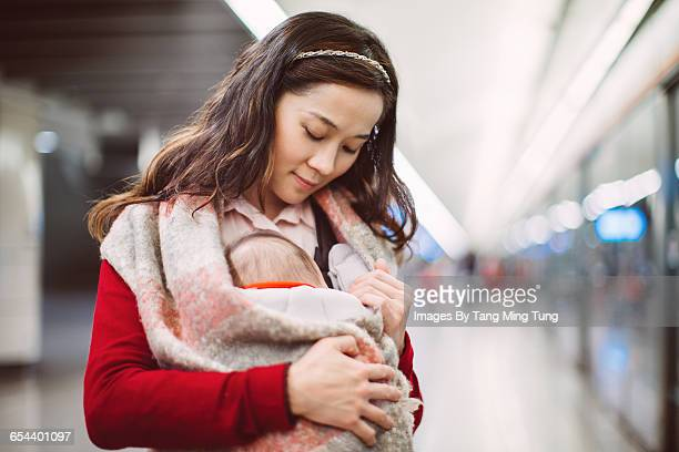 Mom waiting train with baby on railway platform