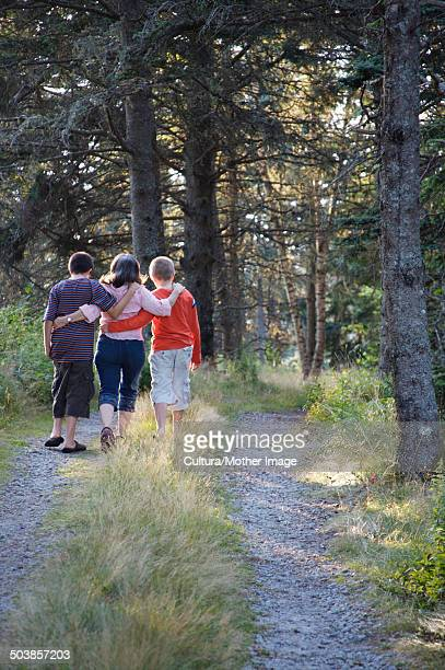 Mom walking with sons in woods
