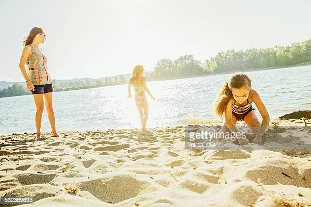 Mom watching kids play at lake beach