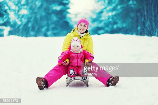 Mom with a child sledding and having fun in winter : Stock Photo