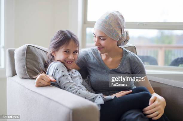 Mom with cancer snuggling on couch with daughter