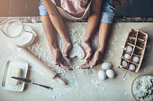 Cropped image of attractive young woman and her little cute daughter are cooking on kitchen. Having fun together while making cakes and cookies. Top view of mom with daughter making dough heart.