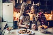 Attractive young woman with her little cute daughter are cooking on kitchen. Drinking milk, eating cakes and cookies.