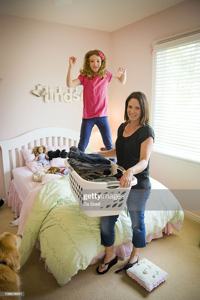 mom with laundry in leaping girl's bedroom : Stock Photo