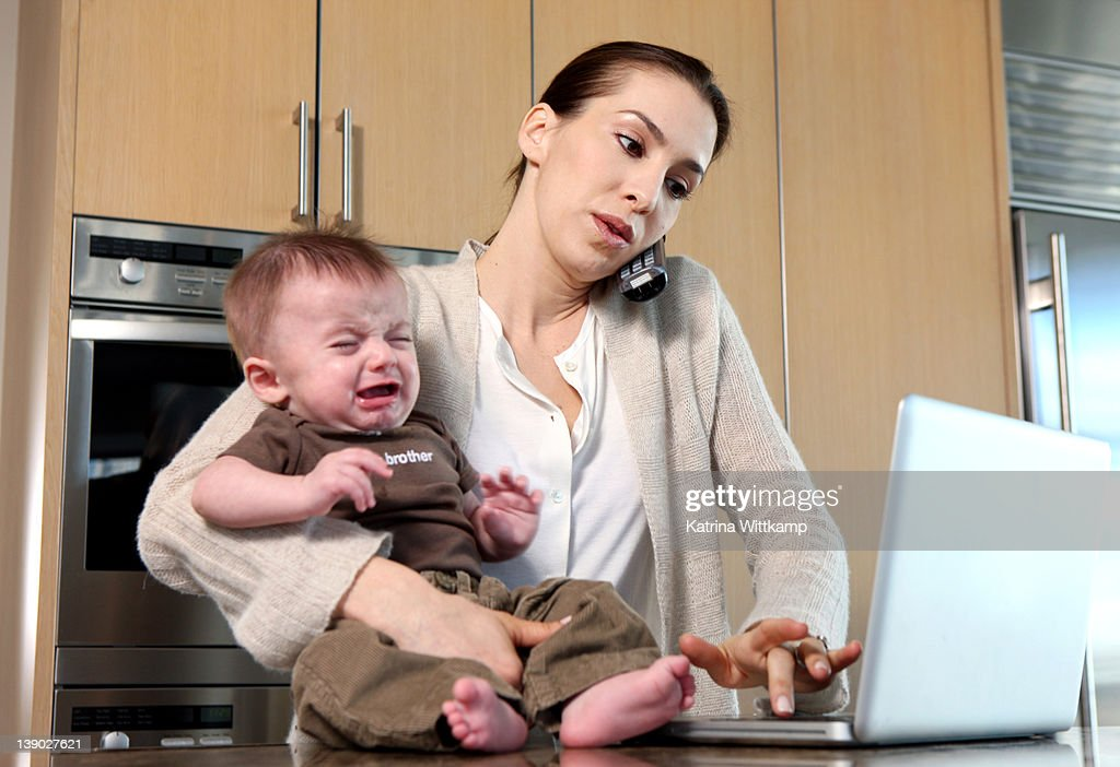 Mom working from home with baby crying : Stock Photo
