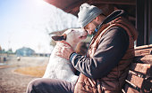 Man sitting on the bench with his dog and sharing moments of  love, happiness and  joy with his bull terrier. Pets and animals. Lifestyle concept