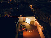 Aerial shot of four friends hanging out and watching movie on a rooftop