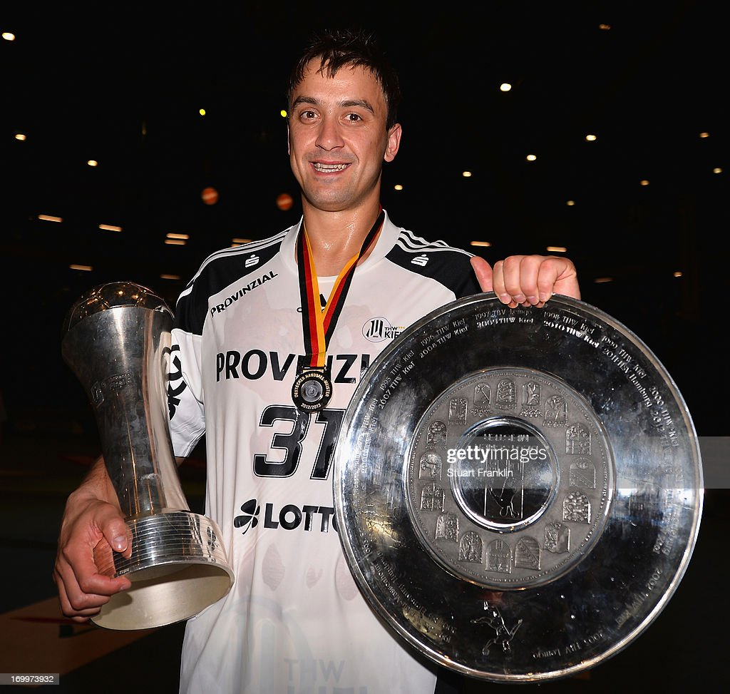 Momir Ilic holds the Cup and the Bundesliga trophy as the players of THW Kiel present the Bundesliga trophy to the fans at the Sparkasse Arena on...