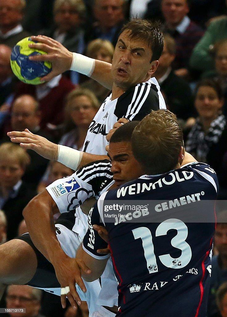 Momir Ilic (back) of Kiel is challenged by Steffen Weinhold (#13) of Flensburg during the DKB Handball Bundesliga match between THW Kiel and SG Flensburg-Handewitt at Sparkassen Arena on November 7, 2012 in Kiel, Germany.