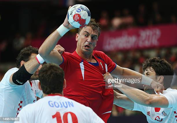 Momir Ilic of Serbia is challenged by Croatia defenders during the Men's Handball Preliminary match between Serbia and Croatia on Day 4 of the London...