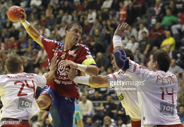Momir Ilic of Serbia throws the ball over Martin Stranovsky and Andrej Petro of Slovakia during the Men's European Handball Championship 2012 group A...