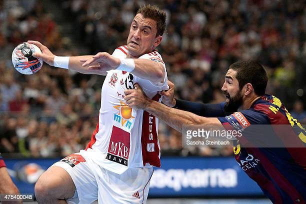 Momir Ilic of Veszprem is challenged by Nikola Karabatic of Barcelona during the 'VELUX EHF FINAL4' final match between FC Barcelona and MKBMVM...