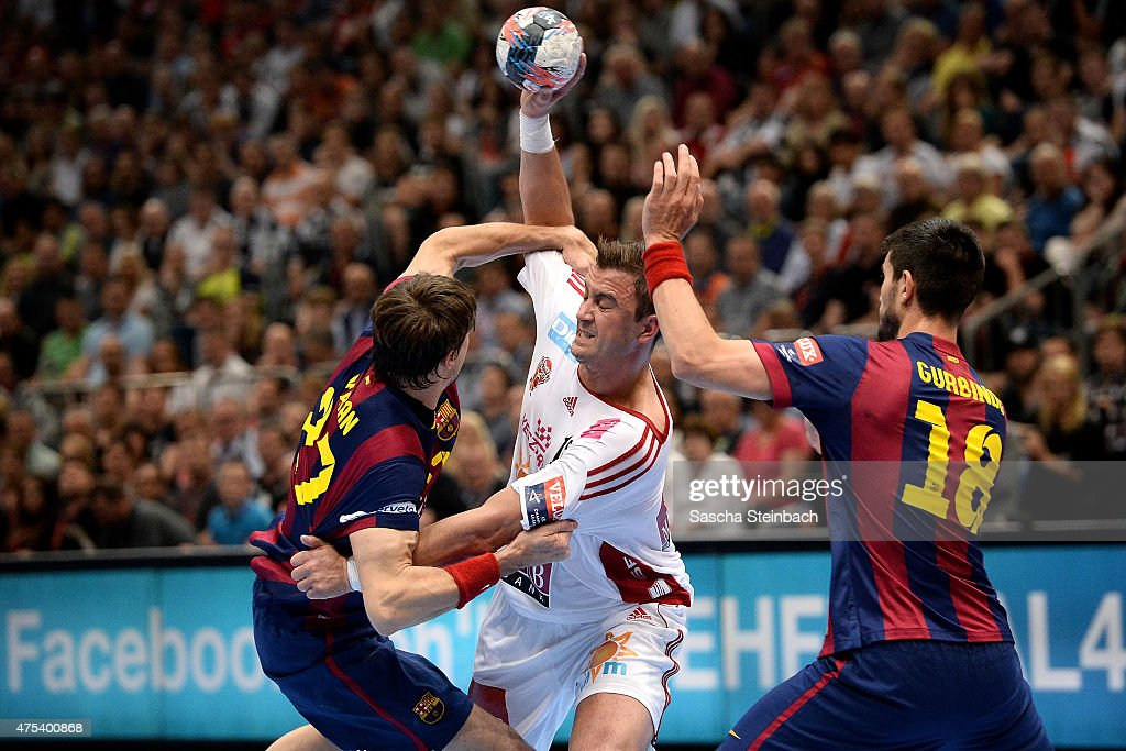 Momir Ilic of Veszprem is challenged by Viran Morros de Argila and Eduardo Gurbindo Martinez of Barcelona during the 'VELUX EHF FINAL4' final match...